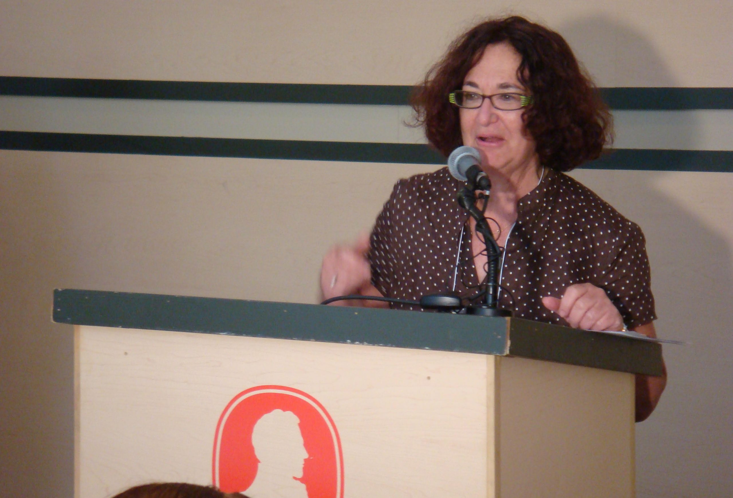 Judy Rebick speaking at a podium
