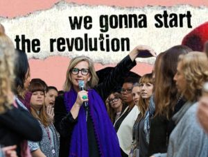 """An image of Vickie Saundersin a blue scarf holding a microphone surrounded by women, text behind her reads """"we are gonna start the revolution"""""""