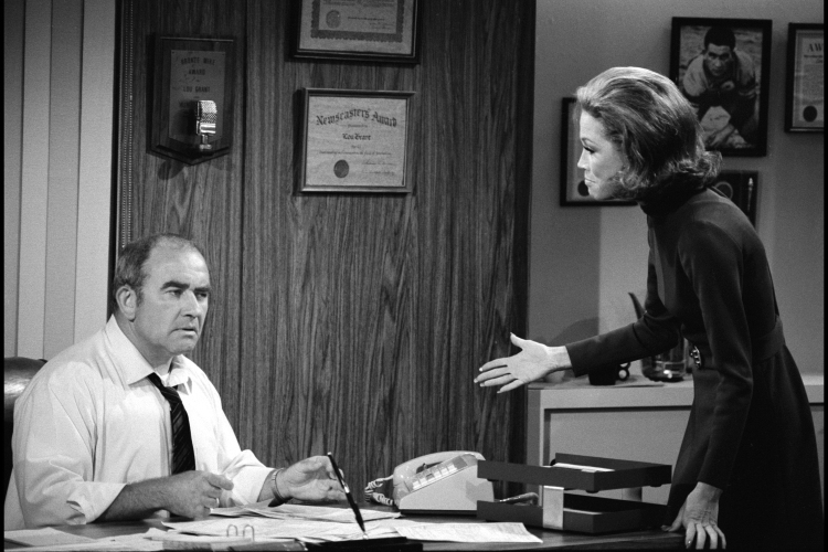 A picture of Lou Grant and Mary Tyler Moore talking about a story