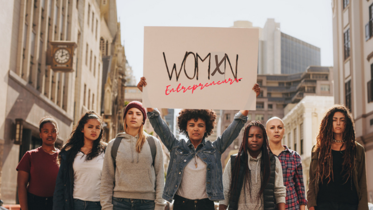 A photo of diverse women holding up a sign that says womxn entrepreneurs