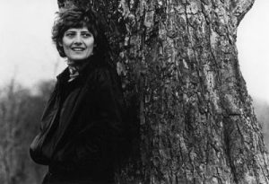 German Green Party Founder Petra Kelly smiling and standing beside a tree
